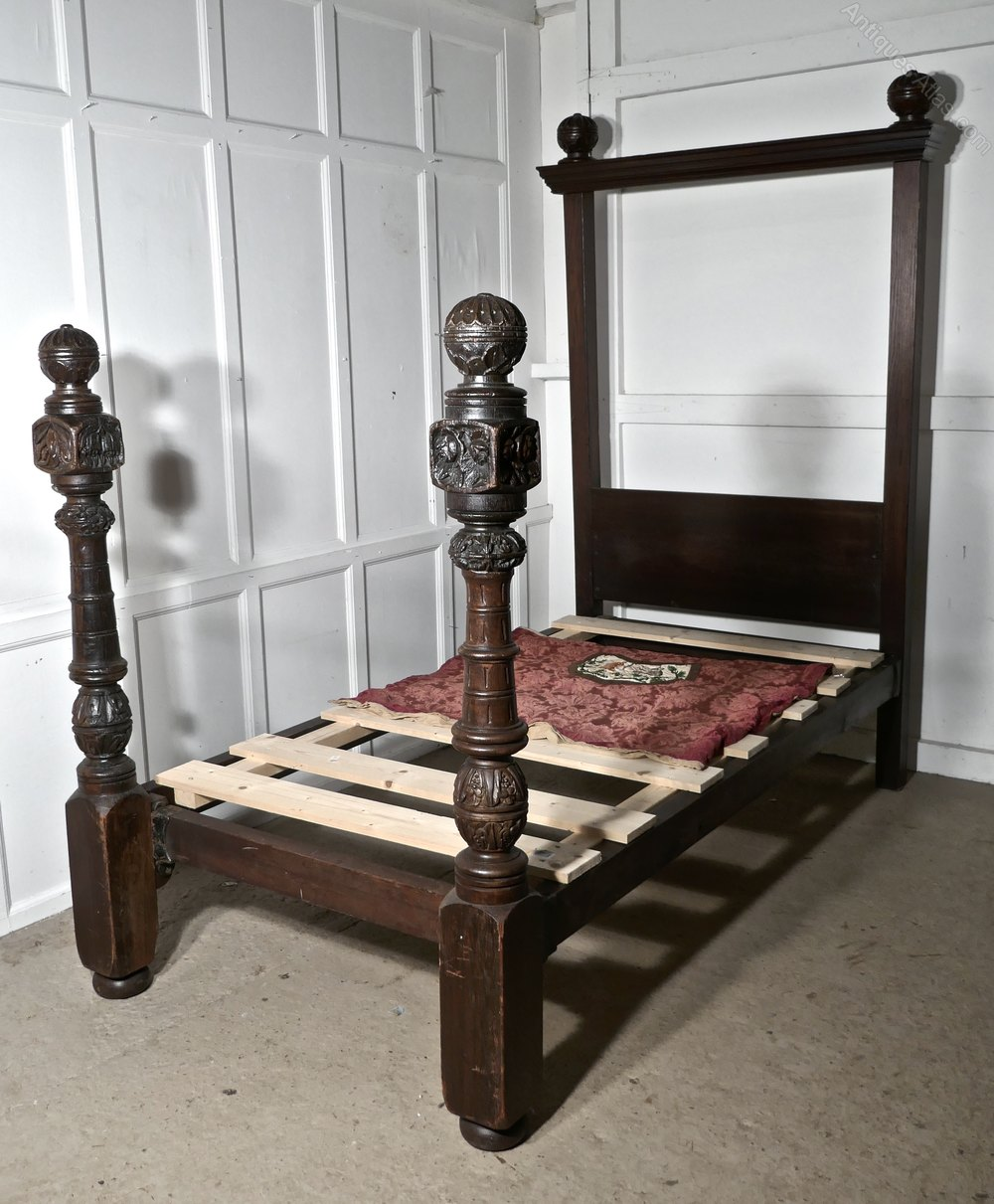 A pair of gothic carved oak poster single beds