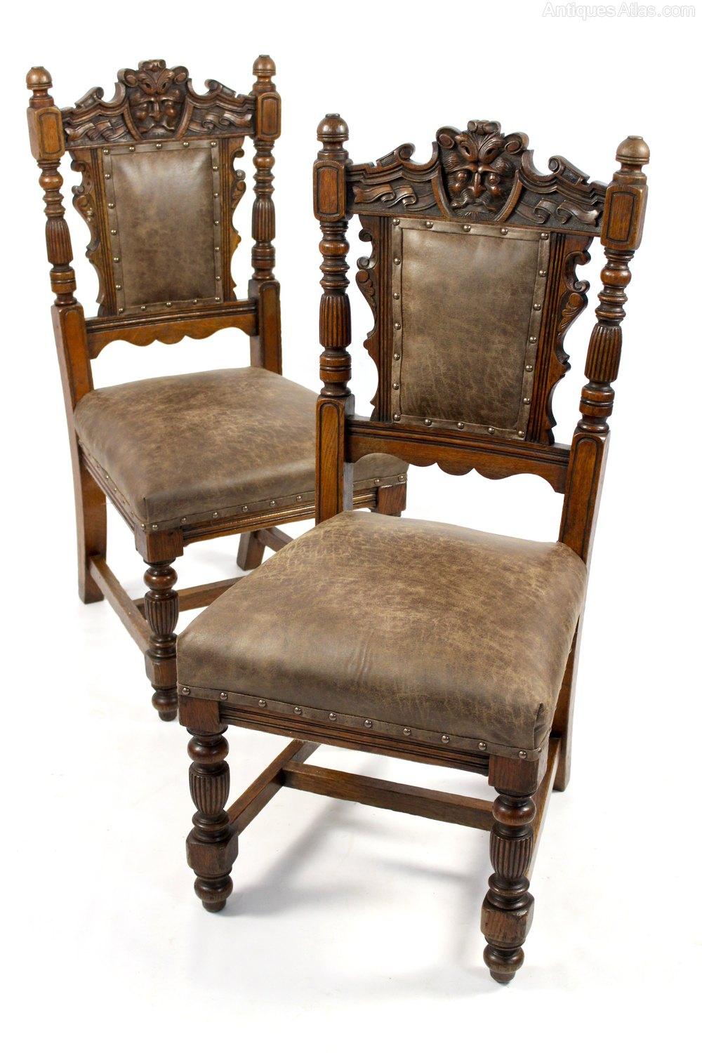 Pair of green man carved oak hall bedroom chairs