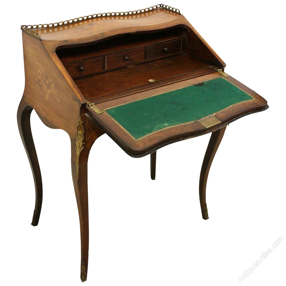 ladies writing desks A vintage drop-front oak ladies writing desk the desk features a glazed finish and antique brass tone hardware there is applied wooden scroll work visible when the desk is closed.